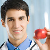 Smiling doctor with apple, at office — Foto de Stock