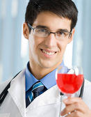 Smiling young doctor with redwine — Stock Photo