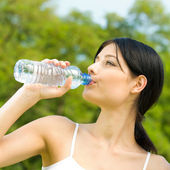 Portrait of woman drinking water outdoor — Stock Photo