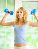 Young happy smiling woman with dumbbells, indoors — Stok fotoğraf