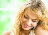 Happy smiling woman talking on cellphone — Stock fotografie