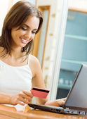 Young woman paying by plastic card, at home — Stock Photo