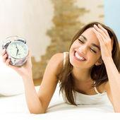 žena s alarmclock na postel — Stock fotografie