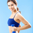 Woman in fitness wear with dumbbell, over blue — Stock Photo