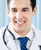 Happy smiling young doctor at office — Stock Photo