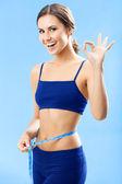 Donna in abbigliamento fitness con nastro, sul blu — Foto Stock