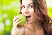 Young woman eating apple, outdoors — Stock Photo