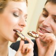 Cheerful couple eating cookies — Stock Photo