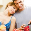 Cheerful young cooking couple at home - Stockfoto
