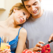 Cheerful young cooking couple at home - Stock Photo