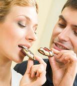 Cheerful couple eating cookies — Stock Photo