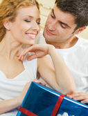 Cheerful amorous couple with gift, indoors — Stock Photo