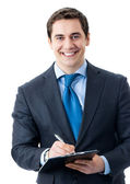 Cherrful businessman with clipboard writing — Stock Photo