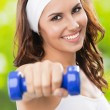 Woman exercising with dumbbell, outdoors — Stock Photo #21300627
