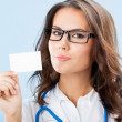 Royalty-Free Stock Photo: Young female doctor showing blank business card