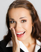 Businesswoman covering mouth, over gray — Stock Photo