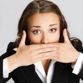 Business woman covering mouth, over gray — Stock Photo