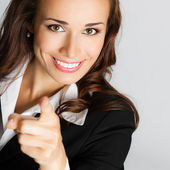 Businesswoman pointing finger at viewer, over gray — Stock Photo