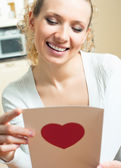 Cheerful smiling woman, reading valentine card — Stock Photo