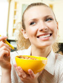 Cheerful woman eating cereal muslin — Stock fotografie
