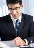 Successful businessman with documents at office — Stockfoto