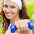 Woman exercising with dumbbell, outdoors — Stok fotoğraf