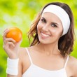Woman in fitness wear with orange, outdoors — Stock Photo #23216492