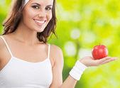 Mujer en fitness desgaste con manzana, al aire libre — Foto de Stock