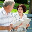 Happy senior couple reading outdoors - Stock Photo