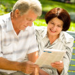 Happy senior couple reading outdoors — Stock Photo #23602275
