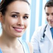Portrait of smiling doctor and female patient — Stock Photo #23602643