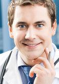 Szczęśliwy uśmiechający się młody lekarz w urzędzie — Zdjęcie stockowe