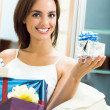 Happy smiling woman with gifts at home — Stockfoto
