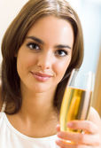 Woman with glass of champagne, at home — Stock Photo