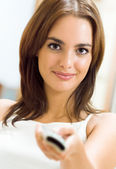 Smiling woman watching TV at home — Stock Photo