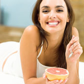Portarit of young woman eating grapefruit at home — Stock Photo