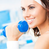 Woman exercising with dumbbell, at fitness center — Stock Photo