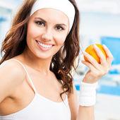 Mulher com laranja, no centro de fitness — Foto Stock