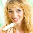 Portrait of young happy woman eating crispbread — Stock Photo #24323475