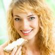 Portrait of young happy woman eating crispbread — Stock Photo