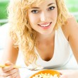 Cheerful woman eating cereal muslin — Stock Photo