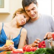 Cheerful young cooking couple at home — Stock Photo #24327715