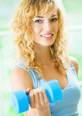 Young happy smiling woman with dumbbells, indoors — Foto de Stock