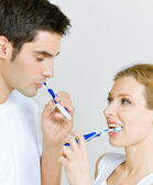 Cheerful young couple cleaning teeth together — Stock Photo