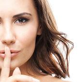 Kvinna med fingret på läpparna, på vitt — Stockfoto