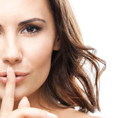 Woman with finger on lips, on white — Stockfoto