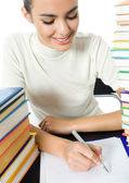 Writing woman with textbooks, isolated on white — Stock Photo