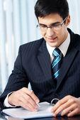 Πορτρέτο της γραφής χαμογελαστό επιχειρηματίας που εργάζεται στο γραφείο — Φωτογραφία Αρχείου