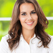 Young smiling cheerful businesswoman at office — Stock Photo