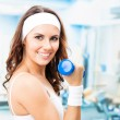 Woman exercising with dumbbell, at fitness center — Stockfoto